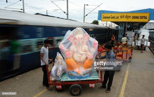 TOPSHOT Indian workers unload an idol of elephant headed Hindu god Ganesha from a passenger train prior to be transported to a place of worship ahead...