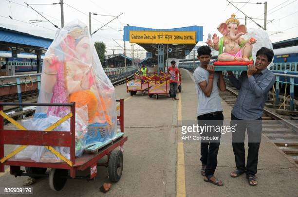 Indian workers unload an idol of elephant headed Hindu god Ganesha from a passenger train prior to be transported to a place of worship ahead of the...