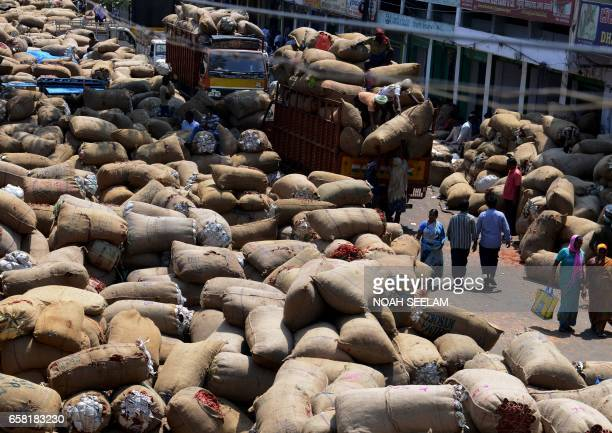 Indian workers unload the crop of dried red chillies at a wholesale market in Hyderabad on March 27 2017 Despite a bumper harvest of red chillies...