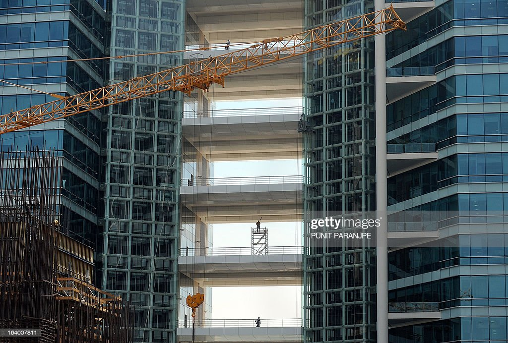 Indian workers walk at an under-construction commercial building in Mumbai on March 19, 2013. India's central bank cut its main interest rate by 25 basis points on March 19, its second such reduction this year in an effort to jumpstart the slowing economy. AFP PHOTO/PUNIT PARANJPE