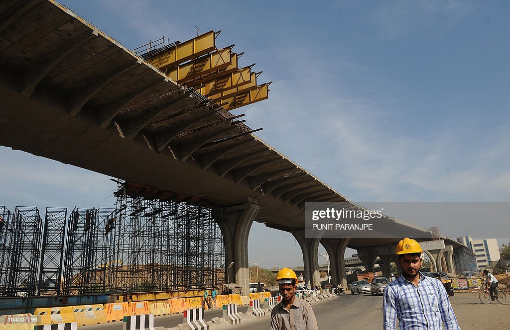 Indian workers walk past an under-construction bridge near the international airport in Mumbai on March 19, 2013. India's central bank cut its main interest rate by 25 basis points on March 19, its second such reduction this year in an effort to jumpstart the slowing economy. AFP PHOTO/PUNIT PARANJPE