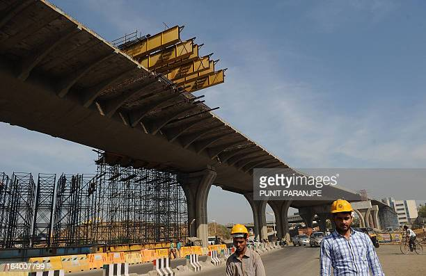 Indian workers walk past an underconstruction bridge near the international airport in Mumbai on March 19 2013 India's central bank cut its main...