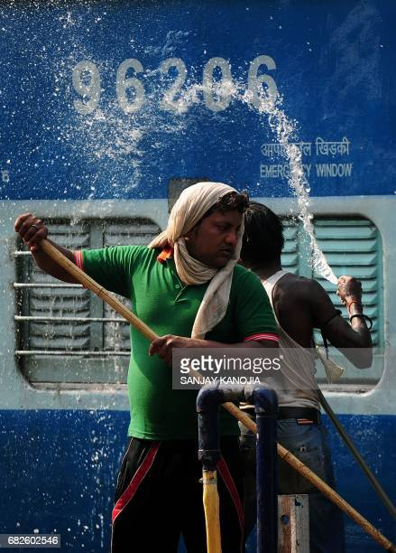 Indian workers wash down a train carriage at Allahabad Railway Station in Allahabad on May 13 2017 / AFP PHOTO / Sanjay KANOJIA