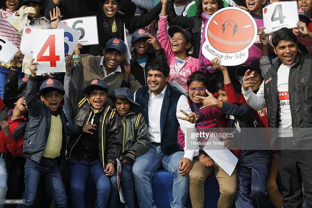 Indian World Champion wrestler <a gi-track='captionPersonalityLinkClicked' href=/galleries/search?phrase=Sushil+Kumar&family=editorial&specificpeople=703954 ng-click='$event.stopPropagation()'>Sushil Kumar</a> sitting with children during T20 match played between members of Parliament and journalists to support childrens health at DPS Mathura Road on December 20, 2014 in New Delhi, India.