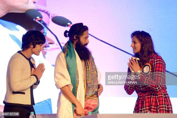 Indian wrestlers Babita and Geeta Phogat appear onstage with Akshar Power Yoga Foundation Master Akshar during a yoga and selfdefence lesson for...