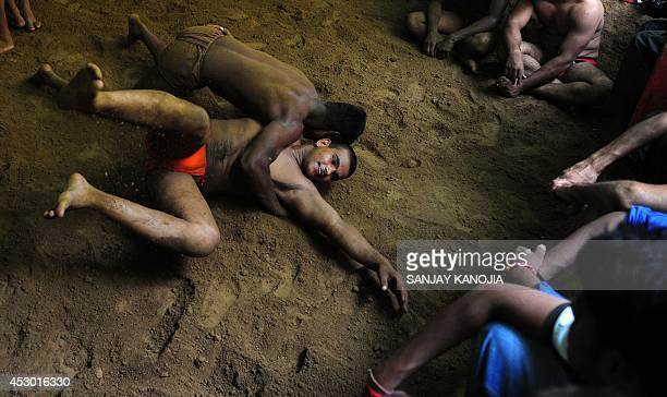 Indian wrestlers perform during a bout of traditional wrestling organized at the historical Loknath Vyayamsala on the occasion of Nag Panchami in...