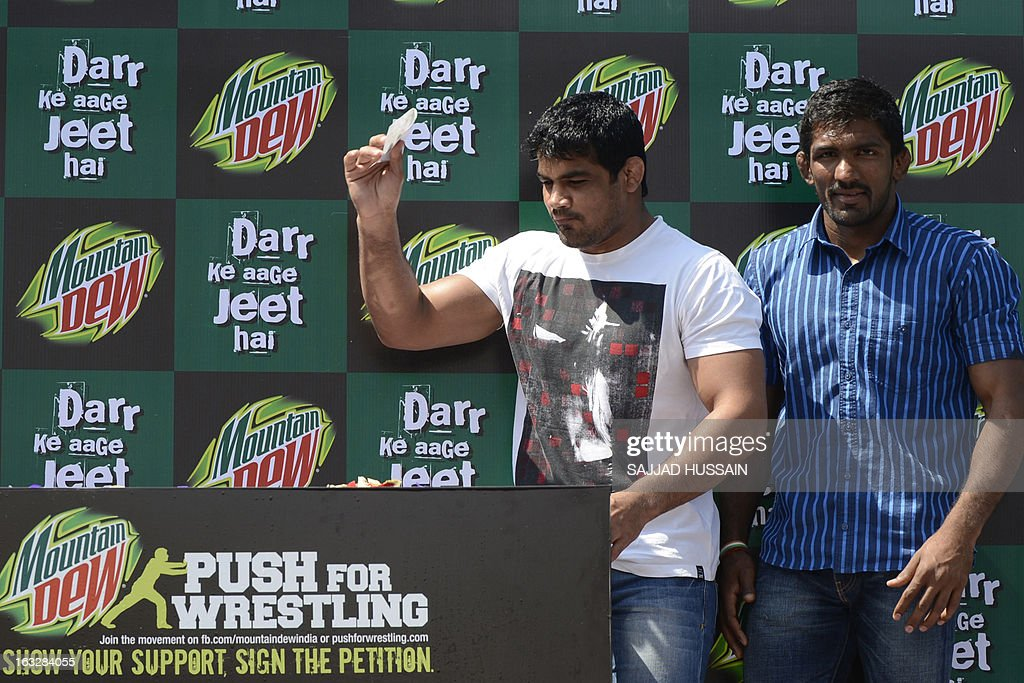 Indian wrestlers Sushil Kumar (L) and Yogeshwar Dutt drop a petition letter into a collection box during a promotional campaign in New Delhi on March 7, 2013, to garner support for reinstating wrestling as a core sport in the Olympics. The International Olympic Committee executive board last month recommended that wrestling be dropped from the 2020 programme.