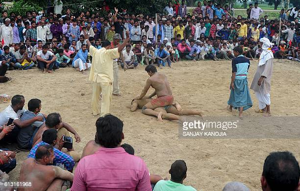 Indian wrestlers take part in a traditional wrestling competition at a local fair held annually in Rampur village near Allahabad on October 7 2016 /...