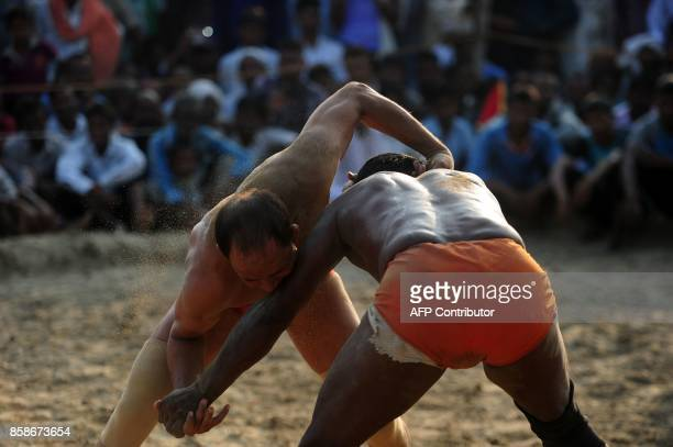 Indian wrestlers take part in a traditional wrestling competition at a local fair held annually in Rampur village near Allahabad on October 7 2017 /...