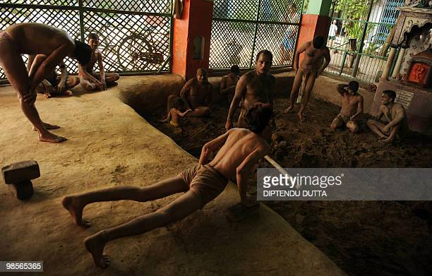 Indian wrestlers warm up at Loknath Akhara in Allahabad on April 19 2010 India's indigenous form of wrestling and once a royal national sport Akhara...