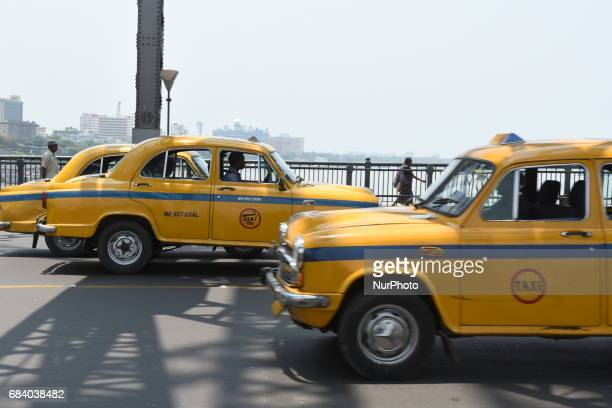 Indian Yellow Ambassador taxis across The Howrah Bridge On May 162017 in KolkataIndia