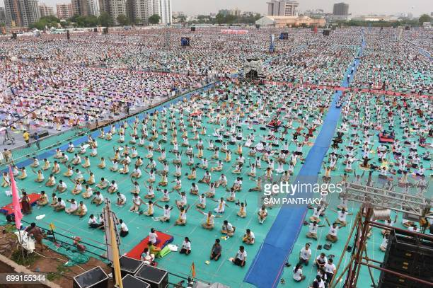 Indian yoga enthusiasts take part in a massive yoga workshop conducted by yoga guru Baba Ramdevji on International Yoga Day in Ahmedabad on June 21...