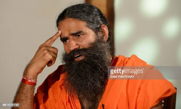 Indian Yoga Guru Baba Ramdev gestures while giving an interview to a television channel after a press conference in Ahmedabad on May 10 ahead of...