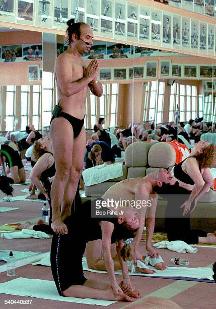 Indian Yoga guru Bikram Choudhury instructs his yoga class as he stands on the hips of student Patrice Baal during a workout in heated room Beverly...