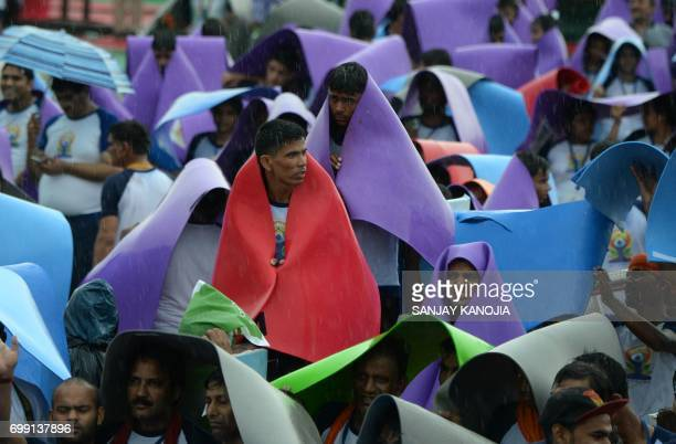 Indian yoga practitioners protect themselves from rain during the 3rd International Yoga Day at Ramabhai Ambedkar Sabha Sthal in Lucknow on June 21...