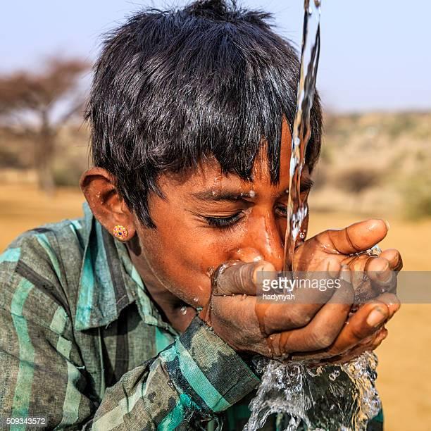 Indian young boy drinking fresh water, desert village, Rajasthan, India