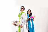 Indian young couple celebrating holi festival. Dancing and playing drums and holding plate full of colours