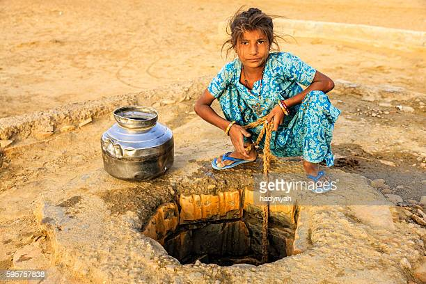 Indian young girl drawing water from a well, Rajasthan
