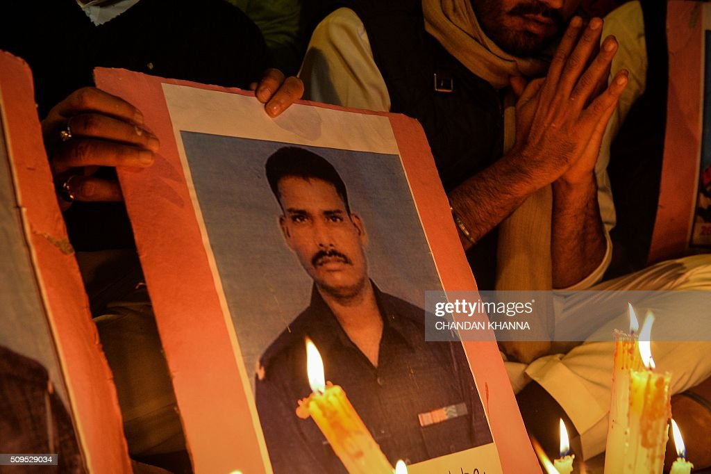 Indian Youth Congress (IYC) activists light candles next to a photo of avalanche survivor Hanumanthappa Koppad in New Delhi on February 11, 2016. Indian soldier Koppad, rescued nearly a week after being buried in eight metres (25 feet) of snow by a deadly Himalayan avalanche, died in hospital on February 11 of his injuries, the army said. AFP PHOTO / Chandan KHANNA / AFP / Chandan Khanna