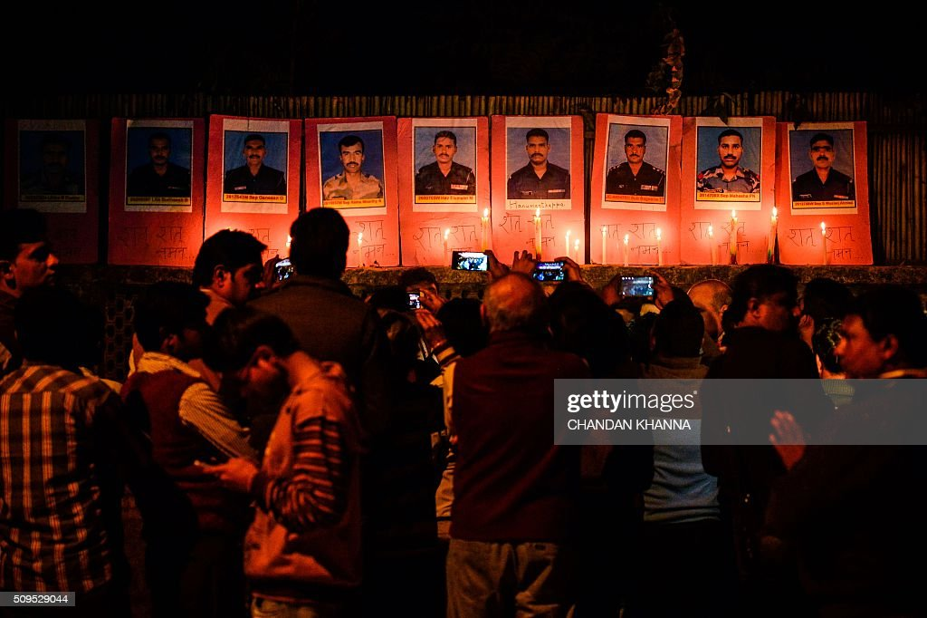 Indian Youth Congress (IYC) activists light candles next to photos of nine Indian army soldiers who died in an avalanche, including the photo of Hanumanthappa Koppad (4th R) who survived for days until he was rescued, before succumbing to his injuries, in New Delhi on February 11, 2016. Indian soldier Koppad, rescued nearly a week after being buried in eight metres (25 feet) of snow by a deadly Himalayan avalanche, died in hospital on February 11 of his injuries, the army said. AFP PHOTO / Chandan KHANNA / AFP / Chandan Khanna