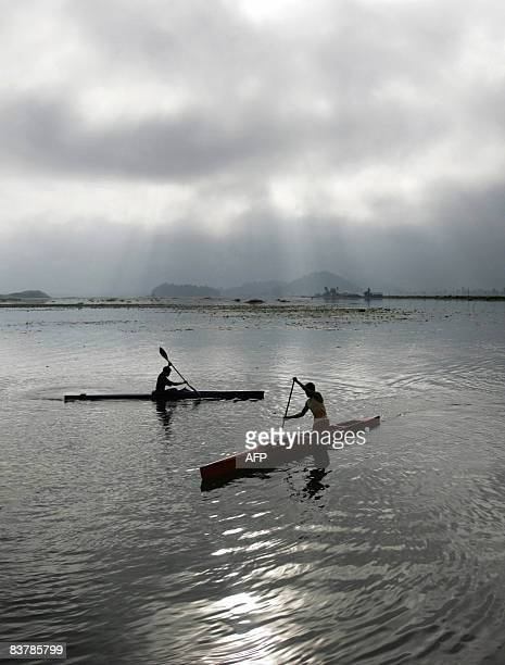 Indian youth paddle their kayaks across Loktak lake some 48 kms southwest of Imphal in Manipur state on November 22 2008 Loktak lake is the largest...