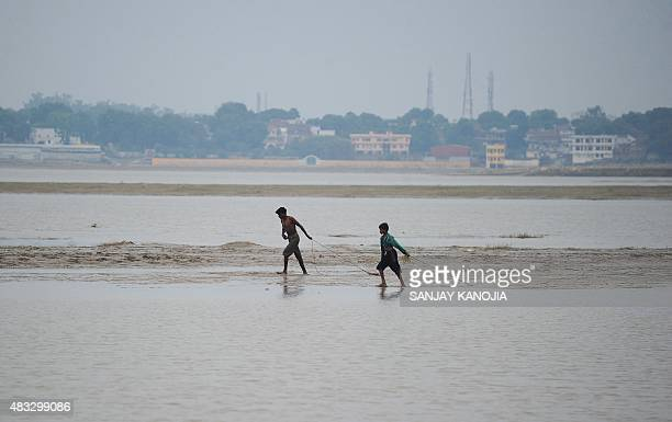 Indian youth search for coins offered by Hindu devotees at Sangam as flood waters recede in Allahabad on August 7 2015 AFP PHOTO/ SANJAY KANOJIA