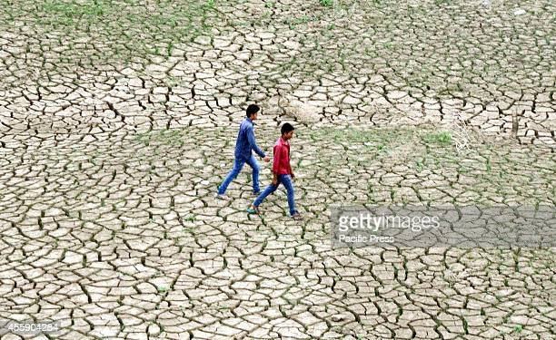 Indian youth walks over dried mud on the banks of a river after waters from the seasonal monsoon rains receded in Allahabad The southwest monsoon...
