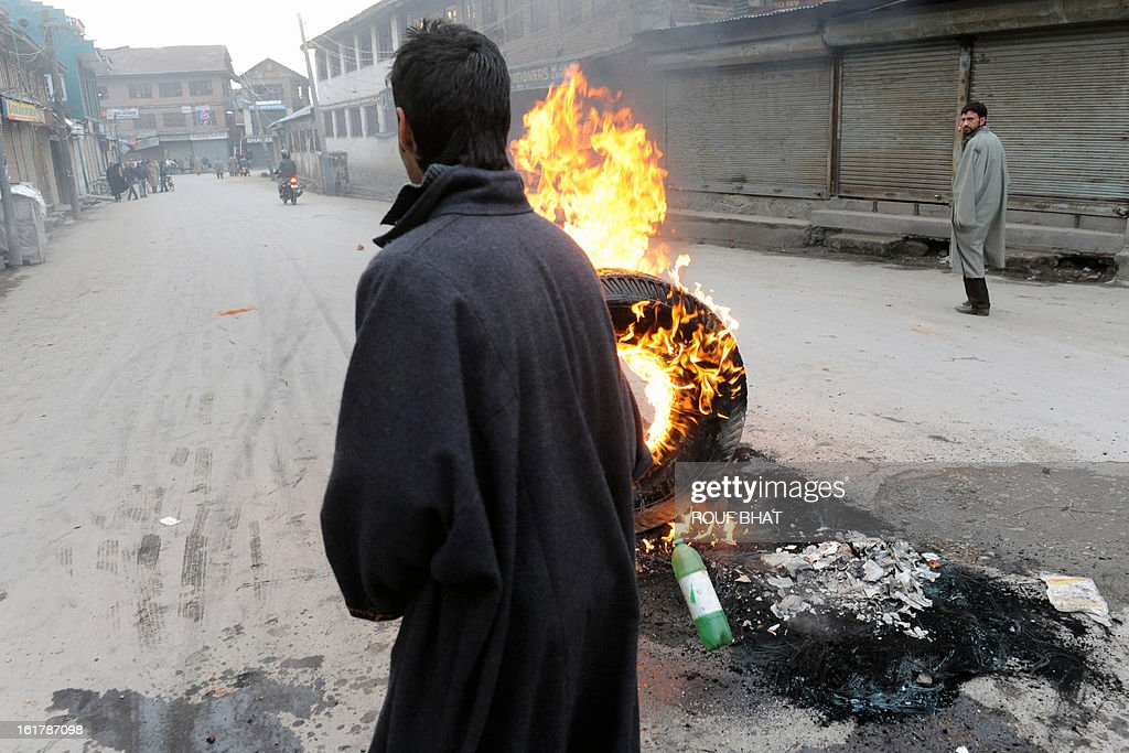 Indian youths burn a tyre during a strike in Srinagar on February 16, 2013. A curfew imposed in Indian Kashmir after the execution of a separatist convicted over a 2001 attack on parliament was lifted Saturday but a strike against the hanging paralysed the region. AFP PHOTO/ Rouf BHAT