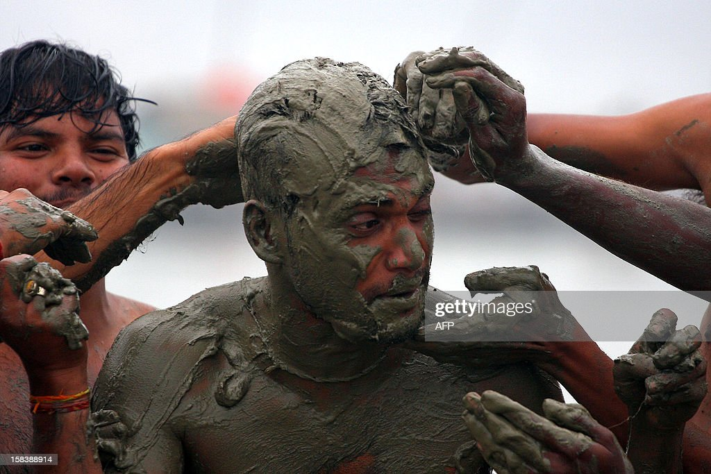 Indian youths cover a friend with mud at Sangam in Allahabad on December 15, 2012. Allahabad, located in the north Indian state of Uttar Pradesh and where the Ganges, Yamuna and Saraswati rivers meet, is a focal point for Hindu pilgrims during The Maha Kumbh Mela, where millions of devotees gather to bathe every twelve years in the holy waters of the three rivers. AFP PHOTO/SANJAY KANOJIA