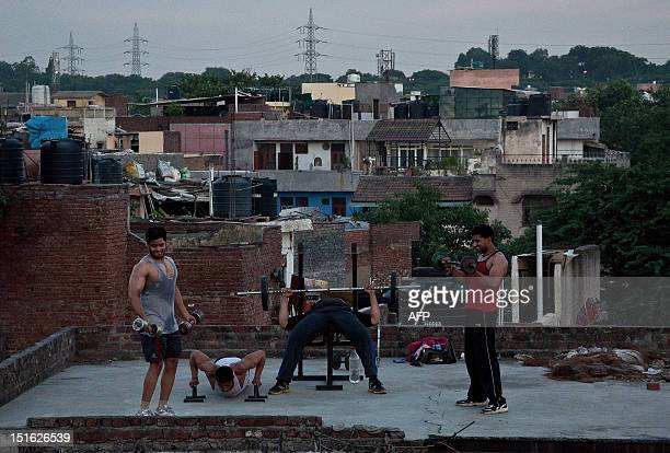 Indian youths exercise on a roof terrace at a residential neighbourhood in New Delhi on September 8 2012 Traditional openair gyms are becoming a rare...