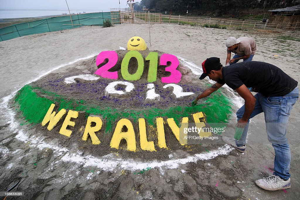Indian youths make an installation to welcome the new year at the banks of the Brahmaputra river in Guwahati on December 31, 2012. Sydney will kick off a wave of dazzling firework displays welcoming in 2013, from Dubai to Moscow and London, with long-isolated Yangon joining the global pyrotechnics for the first time. AFP PHOTO/BIJU BORO