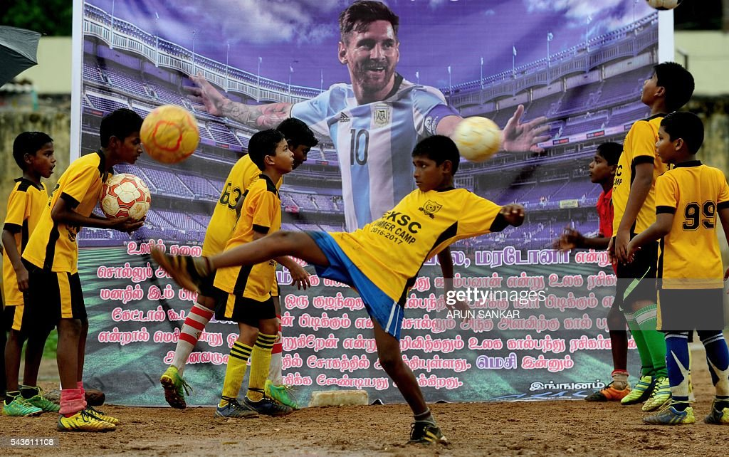 Indian youths play football in front of a poster of Argentinian footballer, Lionel Messi displayed at a football ground and saying that Messi should come back, in Chennai on June 29, 2016. Argentina was defeated in the Copa America final against Chile, 4-2, in a penalty shoot-out. Argentinians begged Lionel Messi - who tearfully decided to quit the international team after missing a spot-kick in the shootout - not to leave the national team despite its traumatic final. / AFP / ARUN