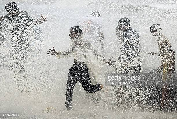 Indian youths play in breaking waves on the seafront during high tide in Mumbai on June 17 2015 AFP PHOTO/ PUNIT PARANJPE