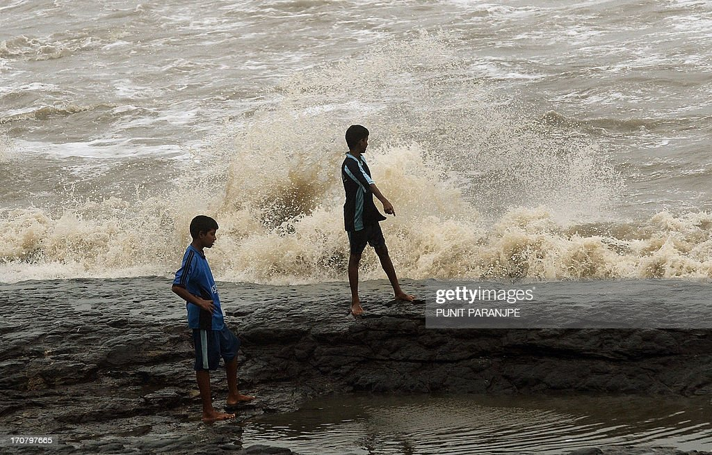 Indian youths play near the sea front during rain showers in Mumbai on June 18, 2013. The monsoon, which India's farming sector depends on, covers the subcontinent from June to September, usually bringing some flooding. But the heavy rains arrived early this year, catching many by surprise. The country has received 68 percent more rain than normal for this time of year, data from the India Meteorological Department shows.