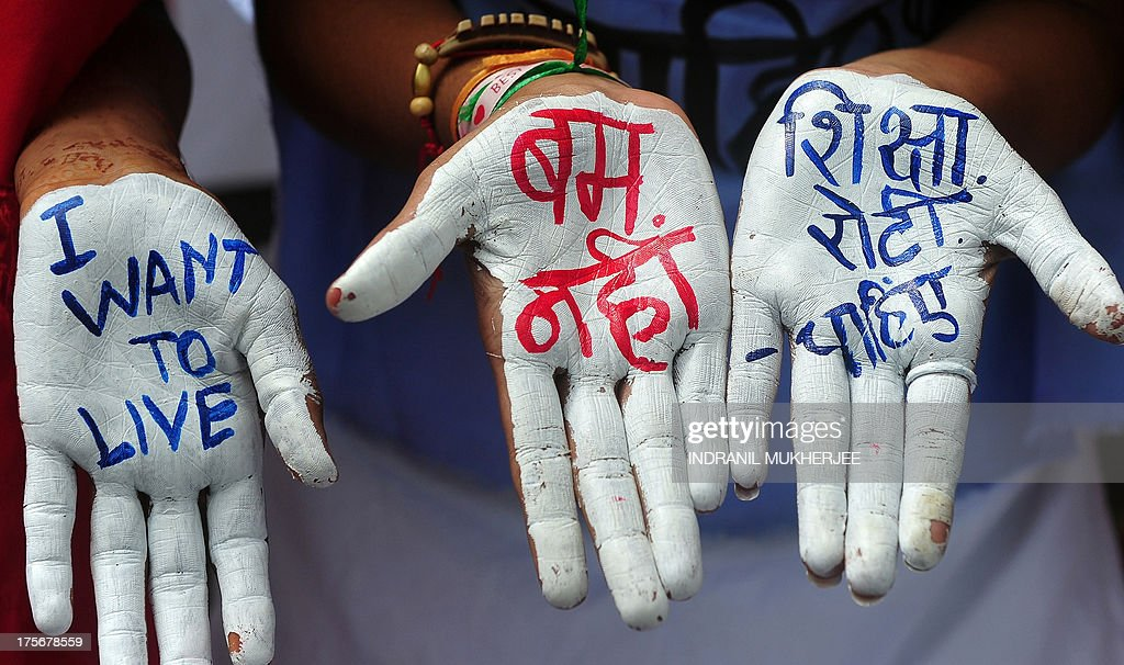 Indian youths pose with their hands painted with peace messages in English and Hindi that read 'no bomb' (C) and 'we want food, education' (R) while taking part in a rally to mark Hiroshima Day in Mumbai on August 6, 2013, to mourn victims of the atomic bombing of Hiroshima in 1945. Peace rallies and memorial services the world over marked the world's first nuclear attack on Hiroshima- the moment 68 years ago when a single US bomb instantly killed more than 140,000 people and fatally injured tens of thousands of others with radiation or horrific burns. AFP PHOTO/Indranil MUKHERJEE