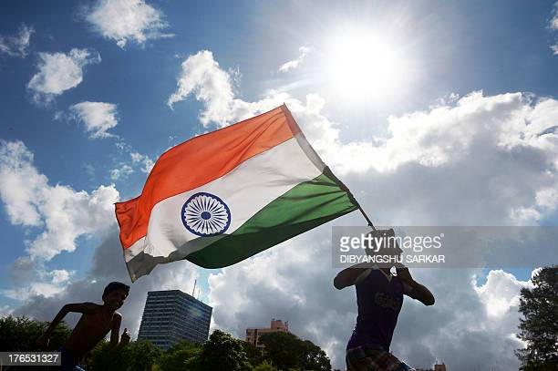 Indian youths run in a field with their national flag as the country celebrates its 67th Independence Day in Kolkata on August 15 2013 Premier...