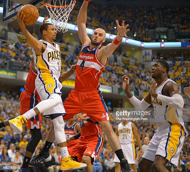 Indiana guard George Hill left has his flight path blocked under the basket by Washington center Marcin Gortat center as the Washington Wizards...