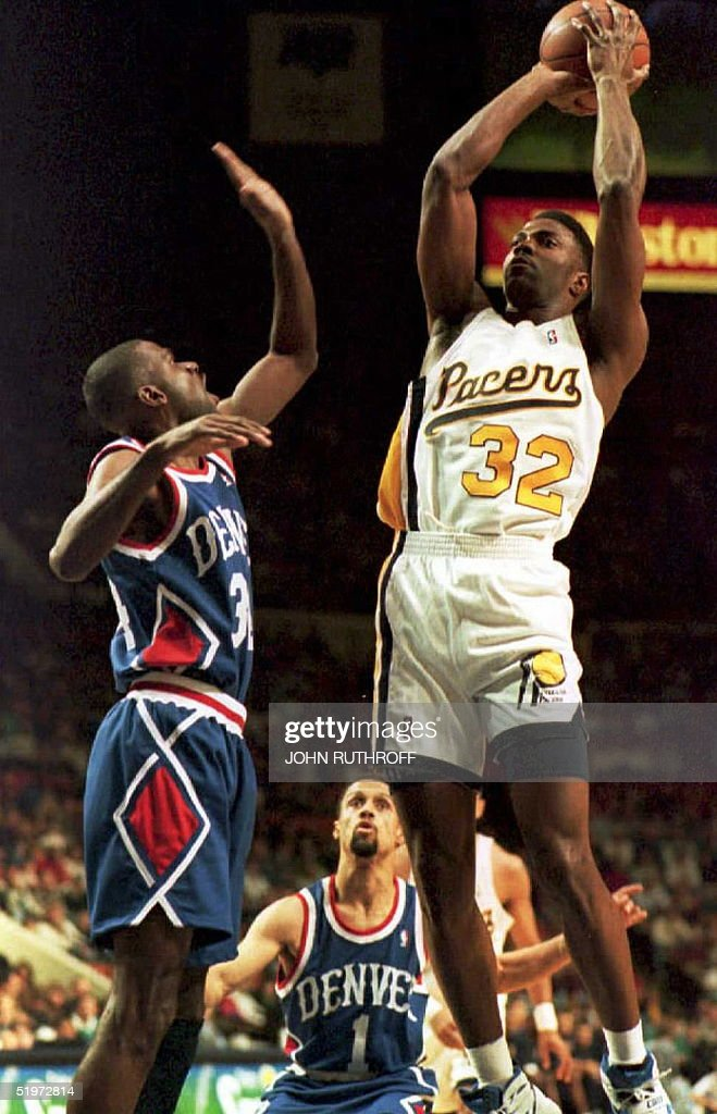Indiana Pacers' foward Dale Davis shoots over the defense of Denver Nuggets' forward Reggie Williams and guard Mahmoud AbdulRauf during the first...