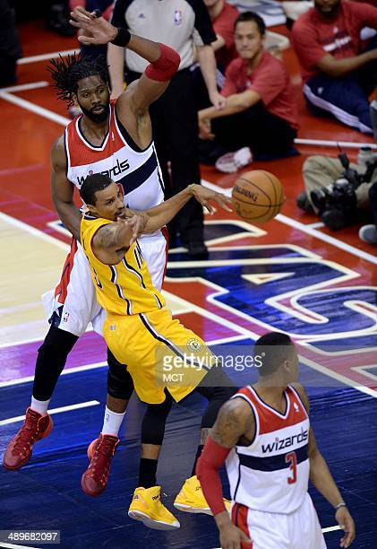 Indiana Pacers guard George Hill dishes the ball off while under defensive pressure from Washington Wizards forward Nene in the second half of Game 4...