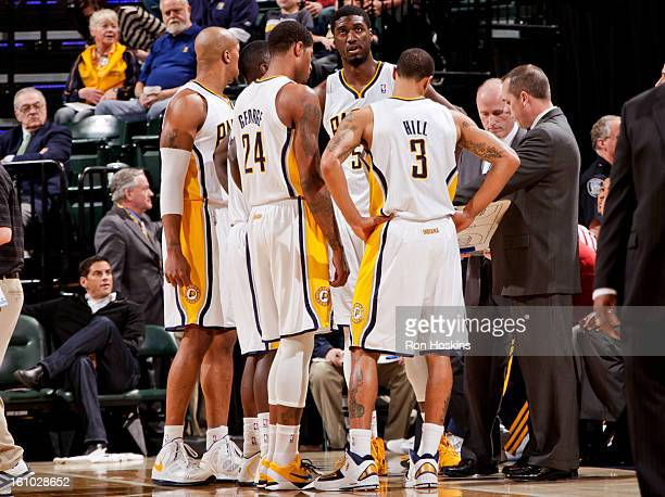 Indiana Pacers players from left David West Paul George Roy Hibbert and George Hill speak with head coach Frank Vogel during a game against the...