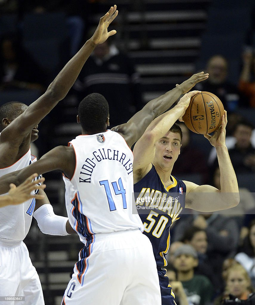 Indiana Pacers' Tyler Hansbrough (50) looks to pass as he gets pressured by Charlotte Bobcats' Bismack Biyombo (0) and Michael Kidd-Gilchrist (14) during the second half at Time Warner Cable Arena on Wednesday, January 15, 2013, in Charlotte, North Carolina. The Pacers won 103-76.