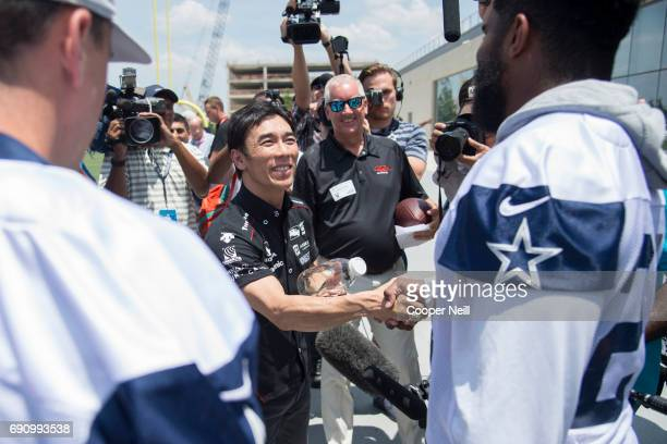 Indianapolis 500 Champion Takuma Sato shakes hands with Ezekiel Elliott after the Dallas Cowboys finished practice at The Star on May 31 2017 in...