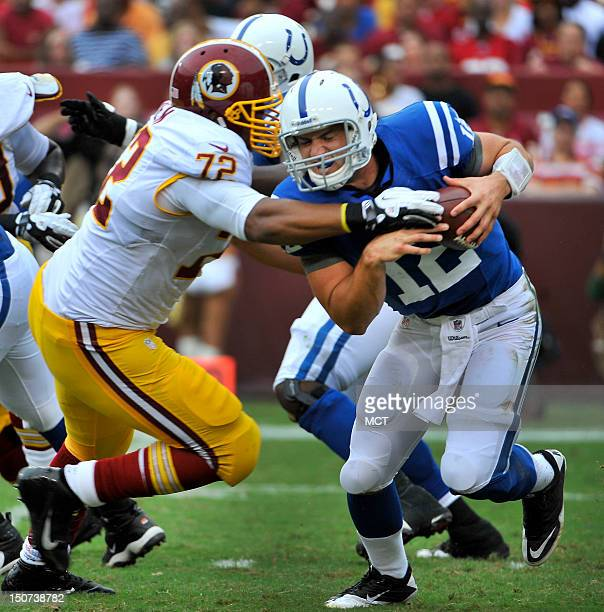 Indianapolis Colts quarterback Andrew Luck comes under pressure from Washington Redskin's Stephen Bowen during the first half of a NFL preseason game...