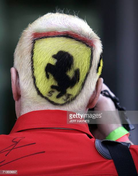 A Formula One racing fan of team Ferrari takes a photograph of the garage area 29 June 2006 at the Indianapolis Motor Speedway the site of the United...
