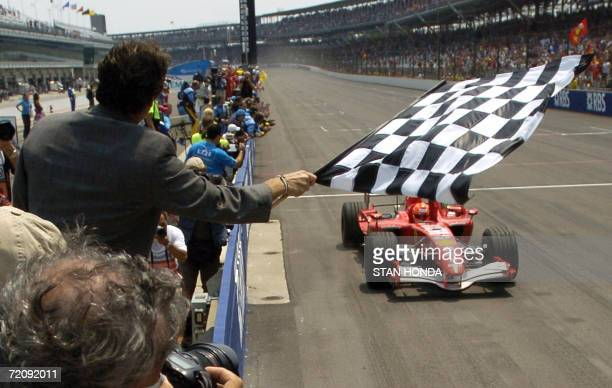 Formula One Ferrari driver Michael Schumacher of Germany takes the checkered flag waved by Tony George CEO of Indianapolis Motor Speedway 02 July...
