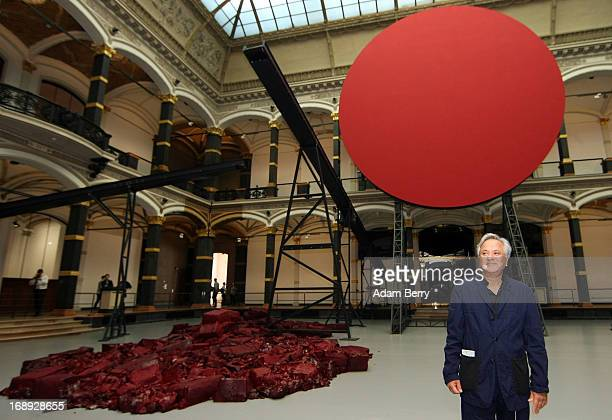 Indianborn British sculptor Anish Kapoor poses in front of his work 'Symphony for a Beloved Sun' prior to the opening of the 'Kapoor in Berlin'...