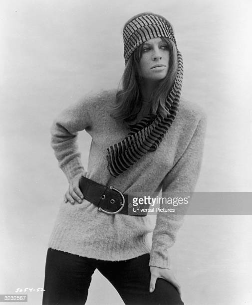 Indianborn English actor Julie Christie poses in a belted sweater a scarf and pants with one hand on her hip and the other hand on her knee in a...