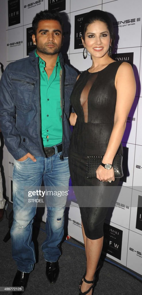 Indian-Canadian film actress Sunny Leone (R) and Bollywood actor Sachin Joshi attend the India Resort wear Fashion Week (IRFW) in Mumbai on December 12, 2013. AFP PHOTO/STR