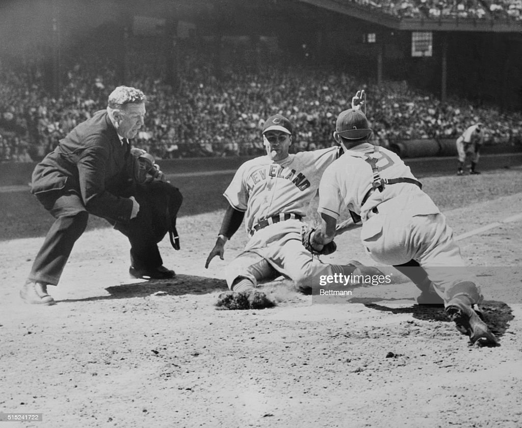 Lou Boudreau, playing manager of the Cleveland Indians, is put on a hard slide at home in the seventh inning of the game with the Philadelphia Athletics June 5. Mike Guerra, A's catcher, nailed him on Ferris Fain's throw home after fielding Walter Judnich's grounder near first base. Umpire is Red Jones. Indians won the opener of an important series with the A's, 7-3.