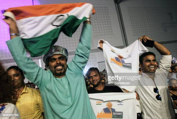 Indians celebrate with a national flag as they attend a speech given by Prime Minister Narendra Modi during a meeting with Indian community at the...